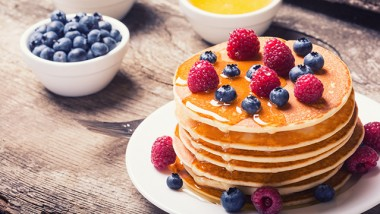 Pancakes with blueberries , honey & raspberry on wood background .