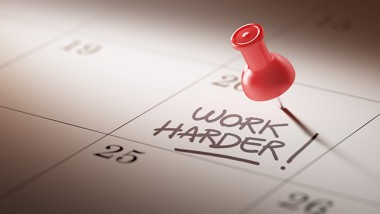 Concept image of a Calendar with a red push pin. Closeup shot of a thumbtack attached. The words Work Harder written on a white notebook to remind you an important appointment.