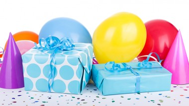 Blue birthday presents with balloons and party hats on white background