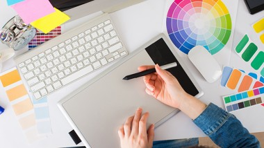 Young pretty Graphic designer using graphics tablet to do her work at desk