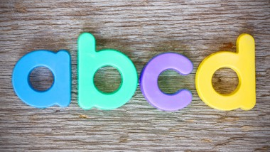 """Letter magnets """"ABCD"""" close up on wood background"""