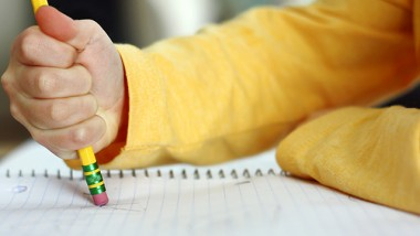 a child has made a mistake while writing and is holding a pencil and erasing on white notebook paper