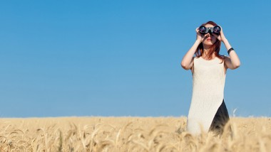 Redhead girl in white dress with binocular at wheat field.