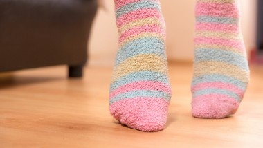 Close up of a person walking on its tip toes, inside bedroom.