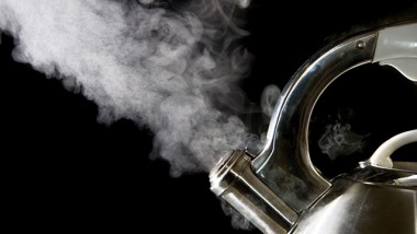 Tea kettle with boiling water; steam against a black background.