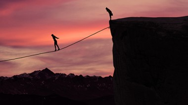 Silhouette of young businesswoman called on all her courage to walk on the rope at mountain. Business challenge concept