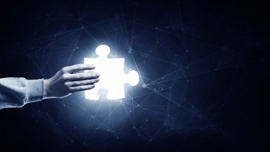 Human hand on dark background holding puzzle glowing element