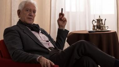 Horizontal view of senior millionaire smoking cigar