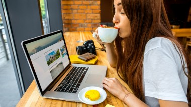 Young woman enjoying cappuccino sitting with laptop in the wooden cafe interior. Coffee break concept