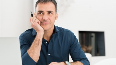 Portrait Of Mature Man Daydreaming While Holding Pen