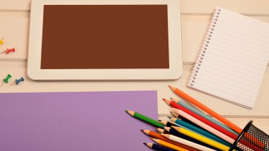 Tablet with paper and colorful pencil on gray wooden table