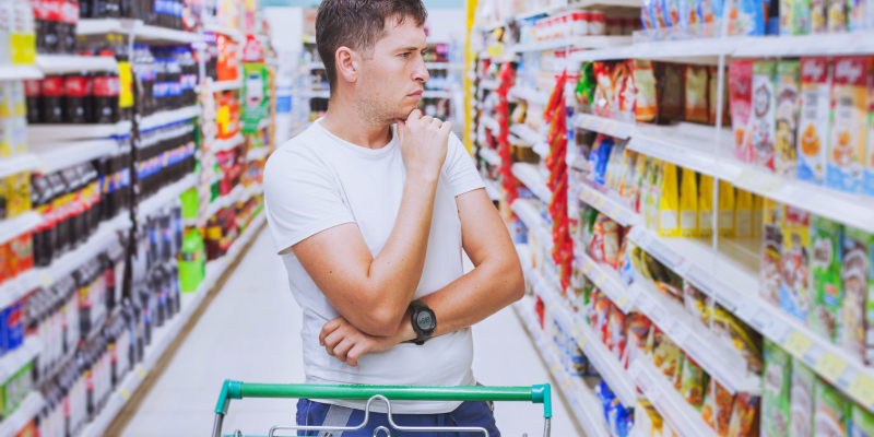 confused man with shopping cart in supermarket