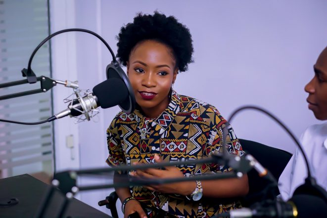 Woman with natural hair and patterned shirt hosting a podcast.